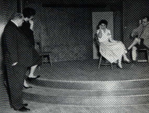 Psicodramma a Beacon (1960). Sul palcoscenico: marito e moglie hanno una discussione. A sinistra, in primo piano: J.L. Moreno dirige la scena. A sinistra, sul gradino: l'Io ausiliario (nella parte della suocera) sta telefonando alla figlia, interferendo nel rapporto di coppia.